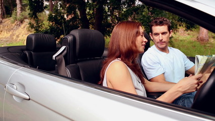 Lost couple looking at a road map in a convertible car