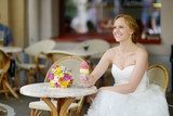 Young bride having an ice cream in outdoor cafe