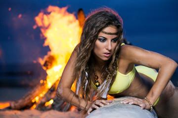 Woman in bikini posing near a bonfire