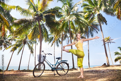 Woman doing yoga near bicycle