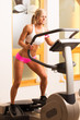 An attractive young woman using a step machine in the gym