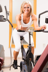 A stunning young woman using an exercise bike in the gym