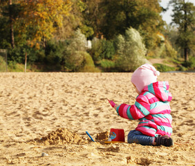 little girl playing with sand at the autumn beach