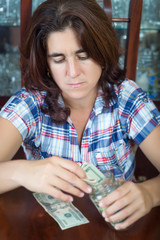 Worried  hispanic woman counting her savings at home