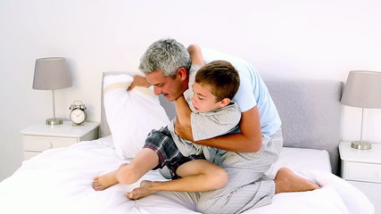 Father and son having a pillow fight in the bed