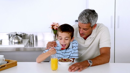 Father teasing son while he is having his breakfast