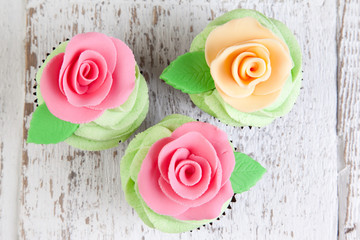 three cupcakes with roses