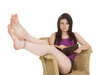 woman purple in chair read legs up
