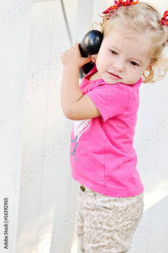 toddler girl speaking on the phone