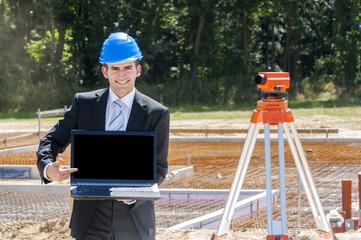 jugner bauingenieur zeigt auf laptopbildschirm