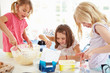 Three Girls Making Cupcakes In Kitchen