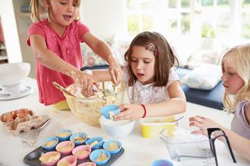 Three Girls Making Cupcakes In Kitchen