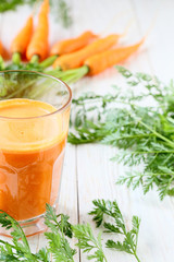 bunch of fresh carrots and a glass of juice