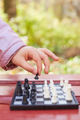 Child hand holds chess piece above chessboard while game in park