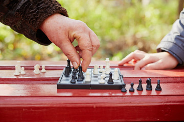 Grandmother hand makes move on chessboard in game in park