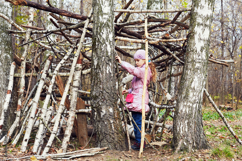 Little girl builds hut between birches in autumn park