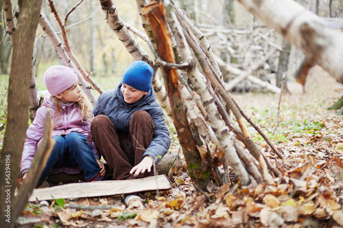 boy and girl sit in hut built between birches in autumn park