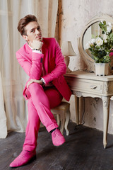 Young man in pink suit and shoes sits on chair with crossed legs