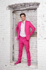 Young man in pink suit and shoes stands with his hands on hips
