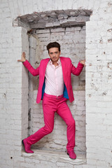 Young man in pink suit and shoes stands with in wall aperture