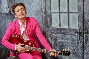 Young man in pink suit sits on armchair and plays guitar