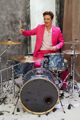 Young man in pink suit plays drums in room powdered with snow