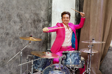 Young man in pink suit plays drums in room corner