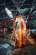 Welder welds steel frame standing on stepladder