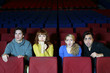 Four young friends look at screen in cinema theater
