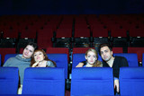 Four young people (two pairs) watch movie in cinema theater.