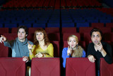 Four young friends amaze and point finger at screen in cinema