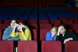 Four young scared friends see movie in cinema theater