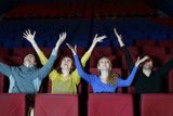 Four happy young friends sit in cinema theater and raise hands
