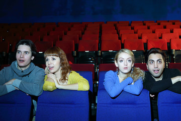 Four young scared and surprised people watch movie