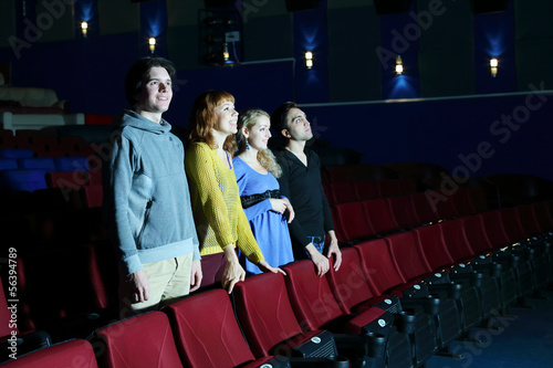 Four happy friends stand and look at screen in cinema theater