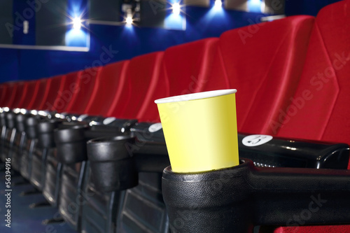 Yellow cup for popcorn is stand at red seat in auditorium