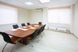 Empty lighting meeting room with long table with papers