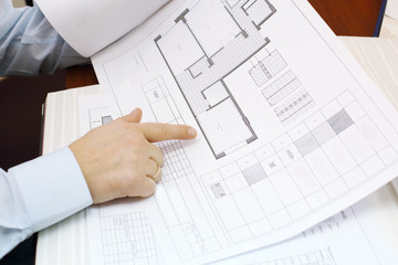 Hands of man looking drawings of apartment