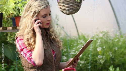 Smiling pretty blonde buying plants following a list