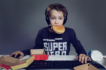enfant mangeant hamburger devant ordinateur