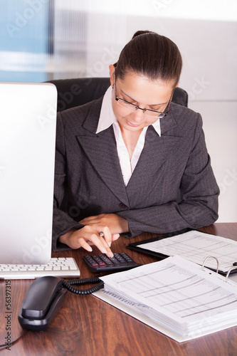 Happy young woman calculating finances