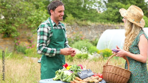 Pretty blonde buying peppers from smiling gardener