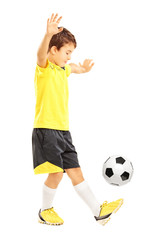 Full length portrait of a boy in sportswear joggling a football