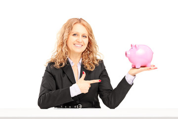 Smiling mature female holding a piggy bank and pointing