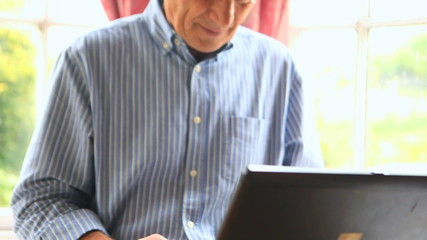Focused mature man sitting by a window using his computer