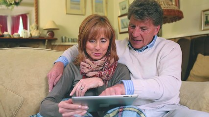 Mature couple sitting on the couch using their tablet pc