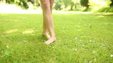 Female legs on the grass walking away