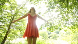 Beautiful teen twirling in the sunlight under the trees