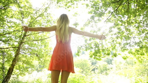 Beautiful teen spinning in the sunlight under the trees