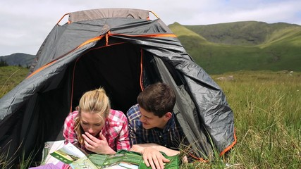 Couple reading map lying in their tent